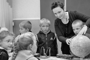 Учитель географии Е.В. Корякина учит детей умению обращаться с глобусом.