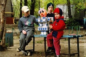 Дети знакомятся с творением искусственного разума: этот робот был изготовлен из пустых пачек от сигарет.